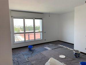 foto esplicativa di come imbiancare la stanza in sicurezza si vede una casa di grande metratura con una finestra e delle coperture per non sporcare a terra